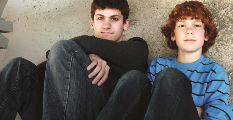 Two boys sitting down outside