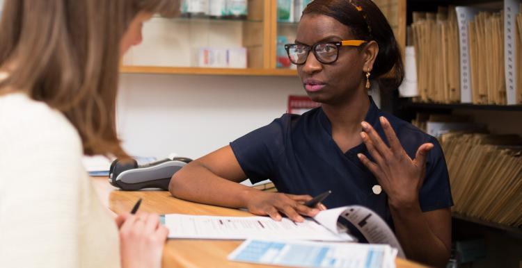 Dental receptionist talking to a customer