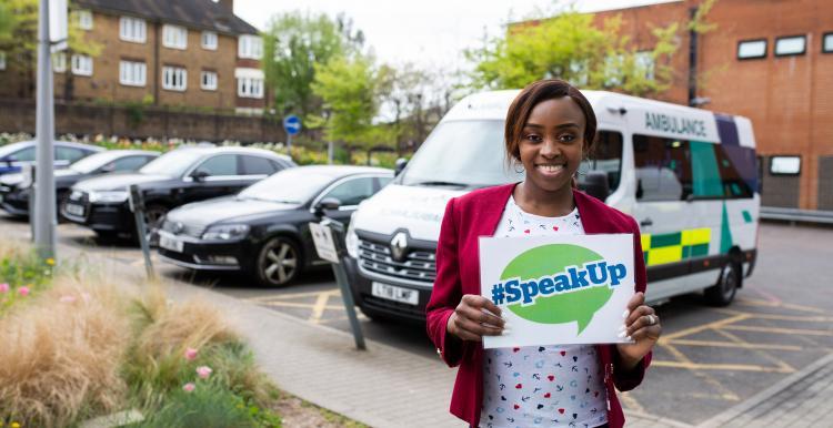 Lady holding up sign saying 'Speak Up'