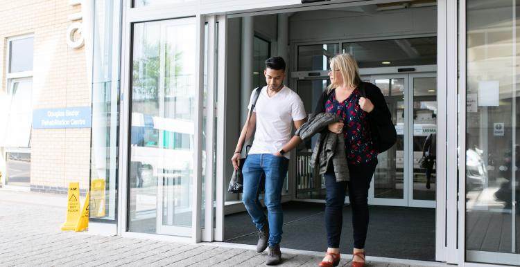 Man and lady walking out of hospital