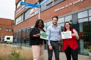 Group of Healthwatch volunteers outside a hospital holding 'Speak up' sign