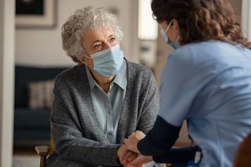 Older lady with face mask on with nurse