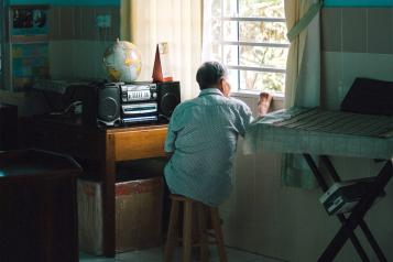 An elderly man looks out a window in the afternoon.