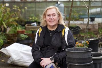 Lady doing some gardening, smiling at the camera. Image from Centre for Ageing Better