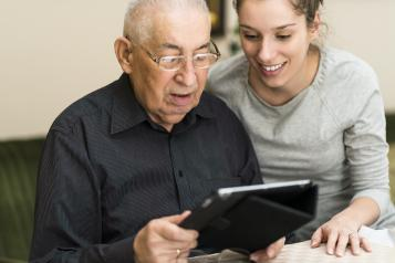 Woman helping an elderly man use a IPad