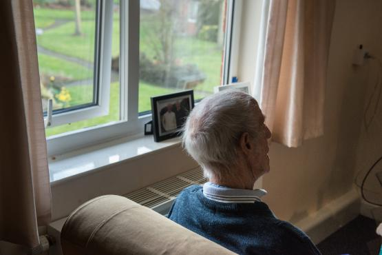 Older man looking out window. Image from Centre for Ageing Better