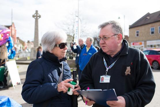 A lady and a man talking with a clipboard