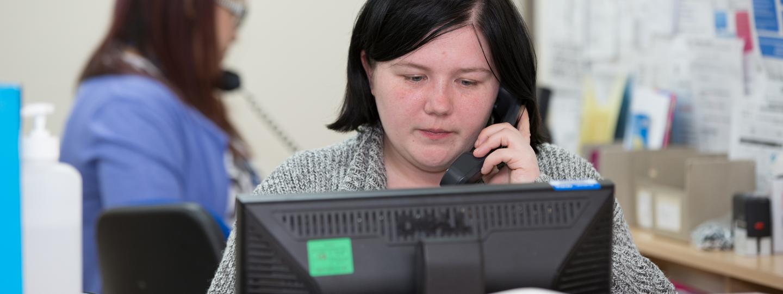GP receptionist talking on the phone