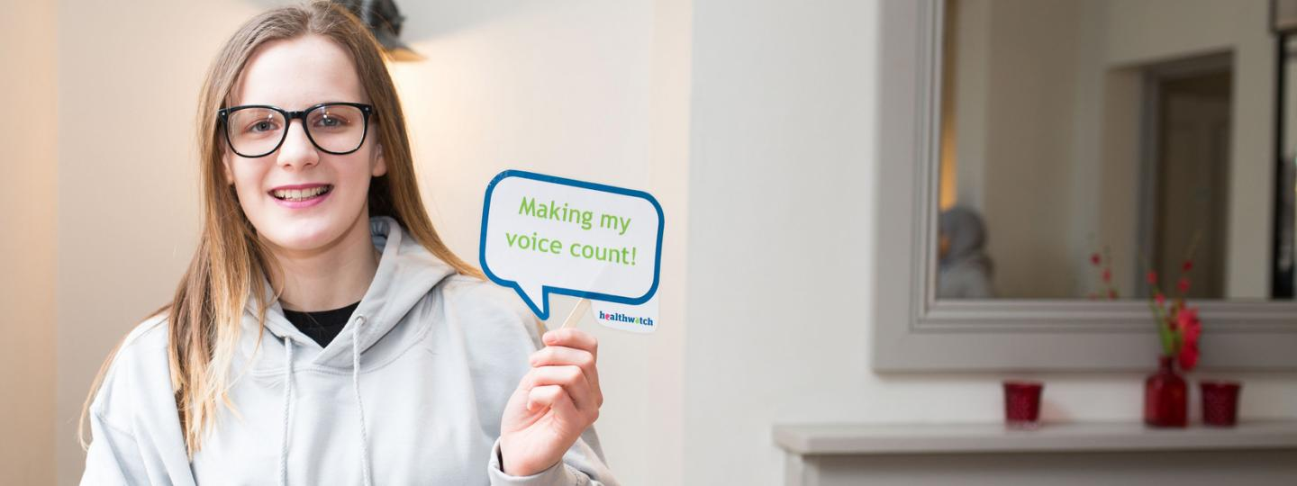 Healthwatch volunteer holding sign saying Making My Voice Count