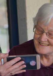 Carer and older person looking at a phone together, smiling