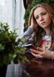 Girl looking sad, holding her phone