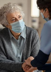 Older lady with face mask on with carer