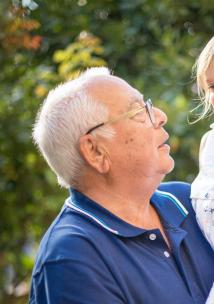 Older man holding his granddaughter