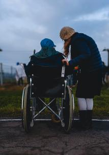 Carer supporting friend in wheelchair